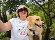 Hispanic adult woman enjoying nature with her pet, a small yellow dog stock photos