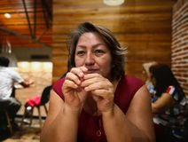 Hispanic adult woman in a restaurant waiting for the food stock photo