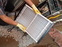 Fixing air conditioner. Hispanic airconditioning repair man performing maintenance Royalty Free Stock Photos
