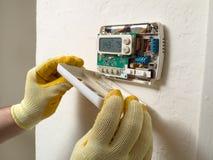 Fixing the thermostat. Hispanic airconditioning repair man performing maintenance Royalty Free Stock Photo
