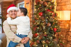 Hispanic Armed Forces Soldier Wearing Santa Hat Hugging Son royalty free stock images