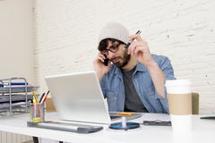 Hispanic attractive hipster businessman working at home office talking on mobile phone Royalty Free Stock Image