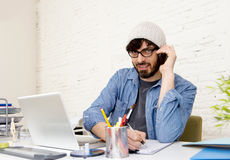 Hispanic attractive hipster businessman working at home office talking on mobile phone Royalty Free Stock Photography
