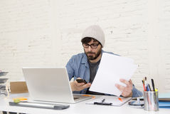 Hispanic attractive hipster businessman working at home office using mobile phone Stock Photos