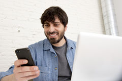 Hispanic attractive hipster businessman working at home office using mobile phone Royalty Free Stock Photo