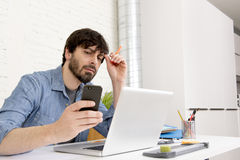 Hispanic attractive hipster businessman working at home office using mobile phone Royalty Free Stock Image