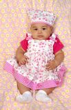 Hispanic baby Girl in pink 3 months old. Vertical portrait of a 3-month-old baby girl in a pink flowery dress sitting on a pink blanket with yellow flower Royalty Free Stock Photo