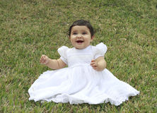 Hispanic Baby in the Grass - 2. Portrait of a little toddler sitting in the grass having a good time in a baptismal gown Stock Image