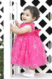 Hispanic Baby playing. Portrait of a Hispanic toddler in a pink dress playing and having a good time Royalty Free Stock Image