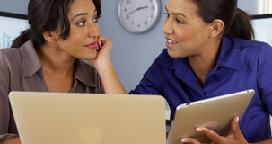 Hispanic and Black women at work in business office. With laptop and tablet computer royalty free stock photo