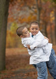 Hispanic boy brothers. Happy young hispanic boy brothers hugging outside in foliage Stock Images