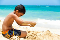 Hispanic boy building a sand castle royalty free stock images