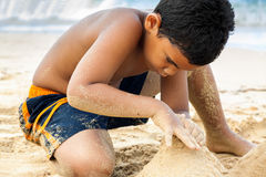Hispanic boy building a sand castle Royalty Free Stock Photos
