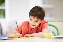 Hispanic Boy Doing Homework In Kitchen Stock Photography