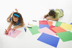 Hispanic boy and girl coloring. Young latino boy and girl coloring on construction paper and smiling Royalty Free Stock Images