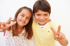 Hispanic Boy And Girl Standing By Wall Making Peace Sign Royalty Free Stock Photos
