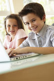 Hispanic Boy And Girl Using Laptop Stock Photography