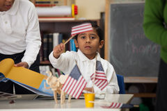 Hispanic Boy in Home-school Setting Waiving USA Flag Stock Images
