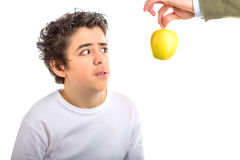 Hispanic boy looks disgusted at an apple offered to him Stock Photos