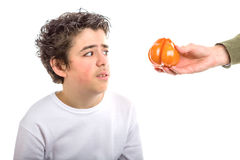 Hispanic boy looks disgusted at a tomato offered to him stock image