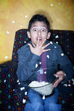 Hispanic boy  with popcorn watching television Stock Photos