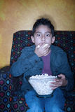 Hispanic boy  with popcorn watching television Royalty Free Stock Image