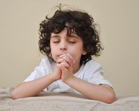Young Hispanic Child Praying and Worshiping God. A Latin child with curly hair praying with reverence and faith during his daily devotional at home Royalty Free Stock Photos