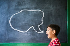 Hispanic Boy Screaming In Classroom With Cloud On Blackboard. Concept on blackboard at school. Young people, student and pupil in classroom. Hispanic boy royalty free stock image