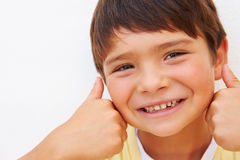 Hispanic Boy Standing By Wall Making Peace Sign Royalty Free Stock Photography