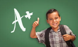 Hispanic Boy with Thumbs Up in Front of A+ Written on Chalk Boar. Cute Hispanic Boy with Thumbs Up in Front of A+ Written on Chalk Board Royalty Free Stock Photo