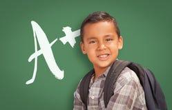 Hispanic Boy Up in Front of A+ Written on Chalk Board Stock Photo