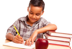 Hispanic Boy Writing with Books, Apple. Adorable Hispanic Boy with Books, Apple, Pencil and Paper Isolated on a White Background Royalty Free Stock Photo