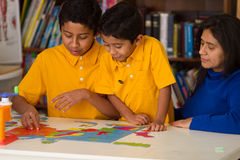 Hispanic Boys and Mom Working on Puzzle. In Classroom stock image