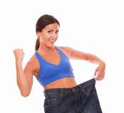 Hispanic brunette female cheerfully pulling jeans. Hispanic brunette cheerfully pulling her jeans to measure waist on isolated background Stock Images