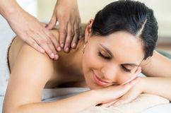 Hispanic brunette model getting massage spa. Treatment, white towel covering upper body lying horizontal smiling to camera Royalty Free Stock Photography