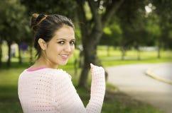 Hispanic brunette model in park wearing white top Stock Photos