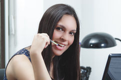 Hispanic brunette office woman sitting by desk and Stock Photos