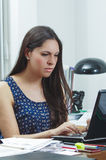 Hispanic brunette office woman sitting by desk and Stock Photo