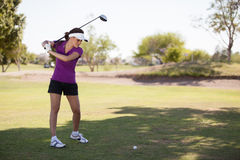 Hispanic brunette playing golf Stock Images