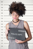 Hispanic brunette rebel model afro like hair. Wearing grey sleeveless shirt holding up police department board with number as posing for mugshot, careless Royalty Free Stock Photography