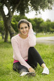 Hispanic brunette sitting on grass in yoga Stock Image