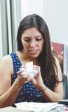 Hispanic brunette sitting by office desk holding Stock Images