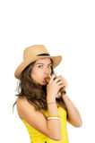 Hispanic brunette wearing yellow football shirt and hat, posing for camera while drinking from beer glass, white studio Royalty Free Stock Image