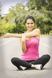 Hispanic brunette in yoga clothing sitting with Royalty Free Stock Photo