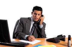 Hispanic Business Man. Handsome young business man in a grey suit at his desk talking on the telephone Royalty Free Stock Photos