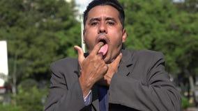 Hispanic business man choking. A young hispanic business man stock video footage