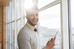 Hispanic Business Man Using Cell Smart Phone Stand in front Panoramic Window Happy Smiling Businessman In Coworking Royalty Free Stock Image
