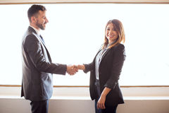 Hispanic business partners giving a handshake royalty free stock photos
