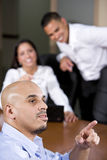 Hispanic business people in boardroom watching. Hispanic business people in boardroom smiling watching presentation, focus on man in foreground royalty free stock photo
