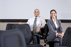 Hispanic business people sitting on office chairs. Professional Hispanic office workers sitting on chairs in boardroom by whiteboard royalty free stock photos